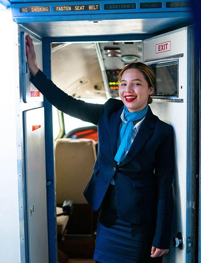 Una azafata de vuelo posa en la entrada a cabina.